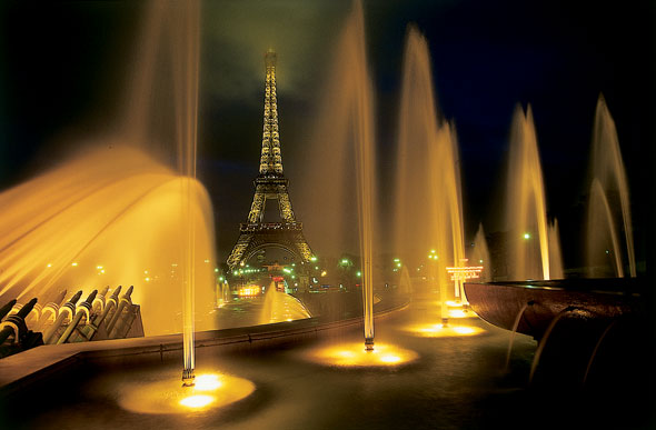 Fountains shimmering in the lights at night with the eiffel tower in the background