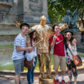 Young students taking a picture with a mime on a golden costume
