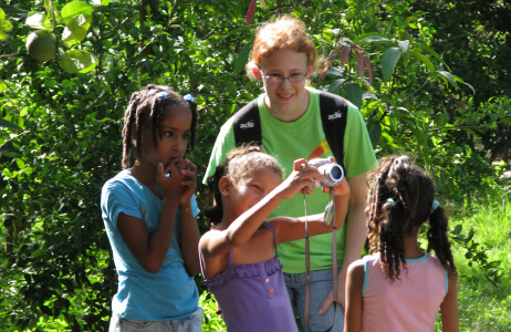 A student with local children on a Service Learning trip