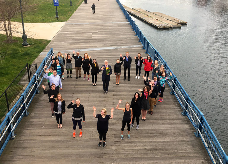 ACIS staff standing together to create a heart