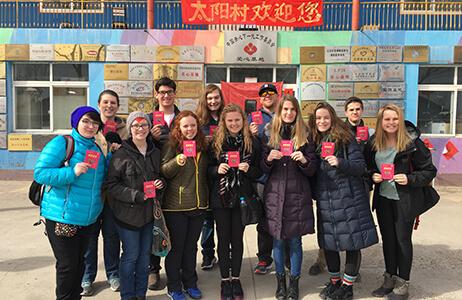 ACIS group standing in front of a school in Beijing