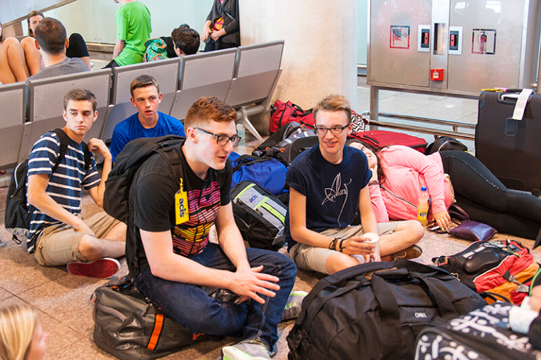 Students waiting at airport with luggage