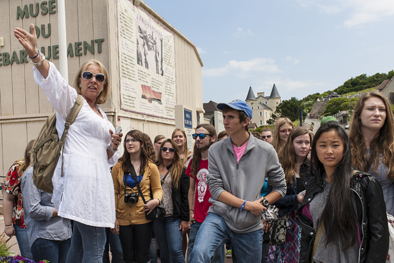 ACIS Tour Manager gesturing with a group next to the Musée du Débarquement in France