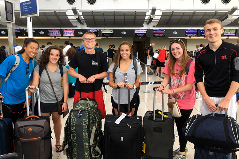 Students pose for the camera in the airport with their suitcases