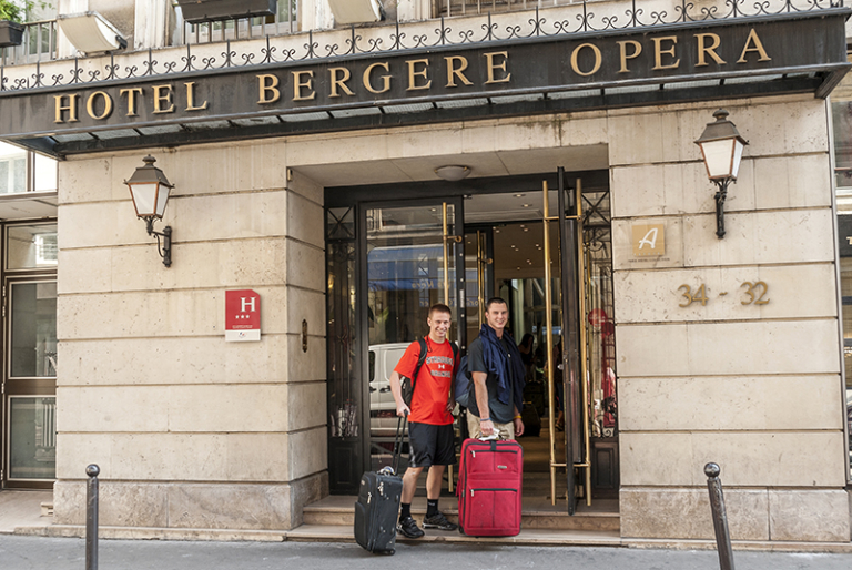 Two students holding suitcases enter the Hotel Bergere Opera