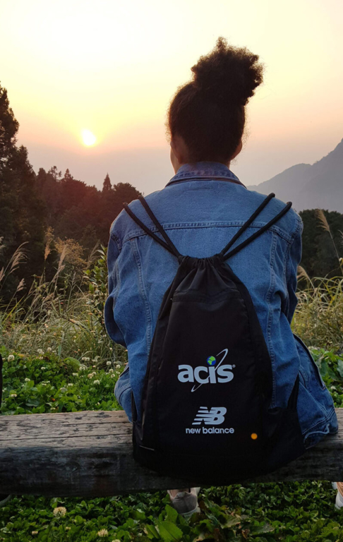 ACIS participant sitting on wood bench overlooking a sunrise