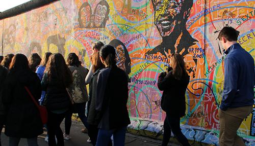Students walk along the Berlin Wall
