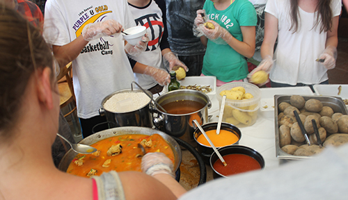 Students participating in a Spanish cooking lesson