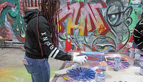 Student spray painting stencil at Berlin Street Art workshop