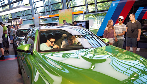 Students inside a car at the Munich BMW factory