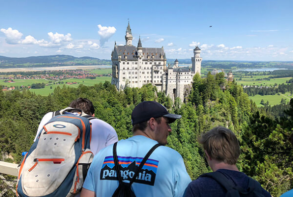 Students and Neuschwanstein castle in the distance