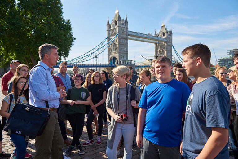 ACIS tour manager speaking with group with London bridge in the background