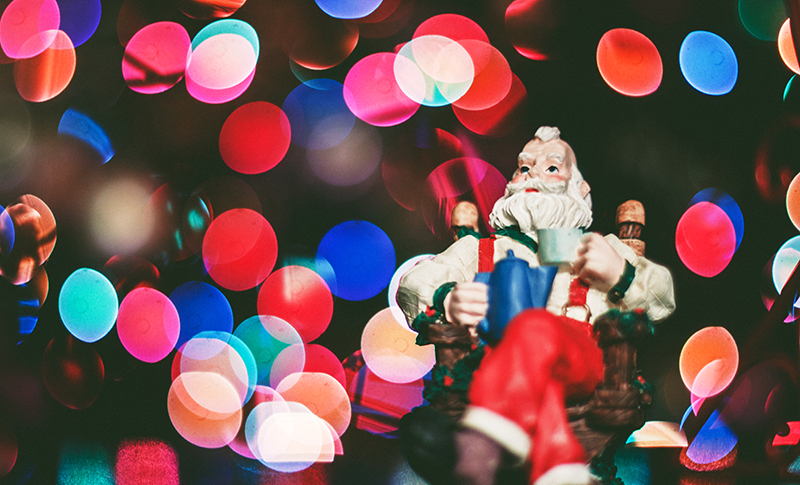 Santa figurine in front of blurry Christmas lights