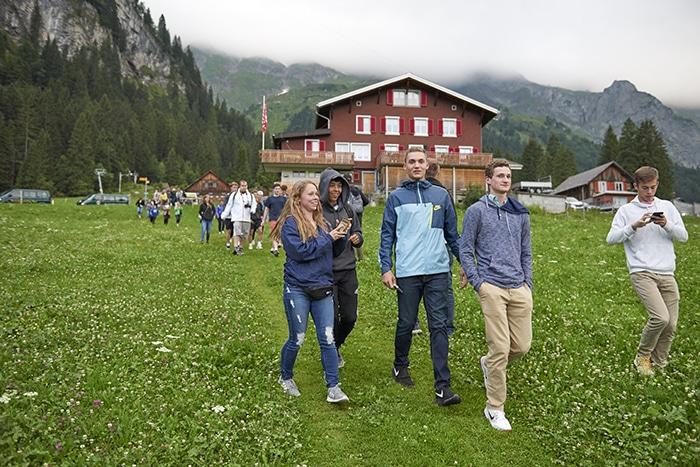 Students walk through a meadow in Engelberg