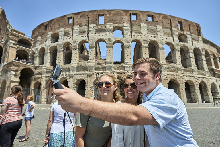 Teens take a photo with the colosseum