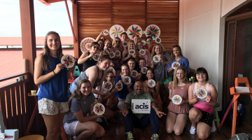 Student group pose with their painted Sarchi souvenirs