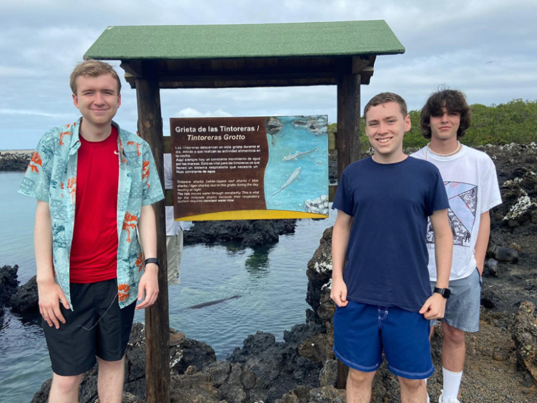 3 ACIS Student travelers standing in front of the Tintoreras Grotto sign in Ecuador