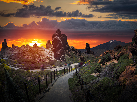 Teide National Park | Description: Road going down landscape with tall rocky formations and scattered bushes, with glowing sunset in background