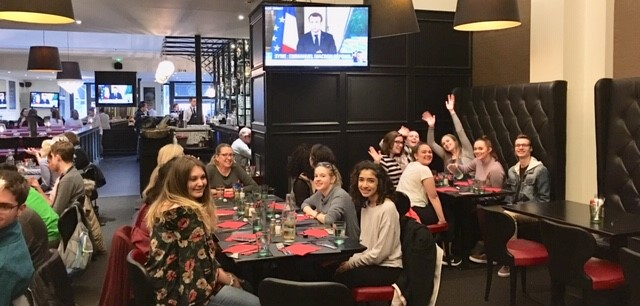 Veronique's student group at a restaurant and smiling for the camera